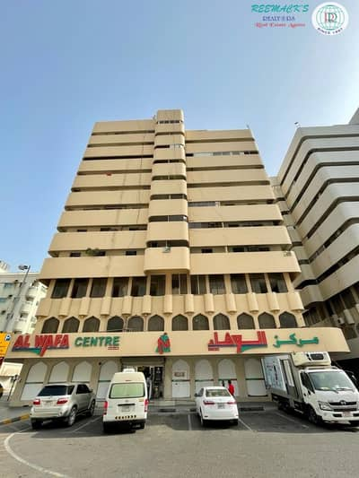 2 Bedroom Apartment for Rent in Al Shuwaihean, Sharjah - 12 months contract and  one month SPACIOUS 2 B/R HALL FLAT WITH SPLIT DUCTED A/C AND BALCONY IN AL WAFA CENTER BUILDING