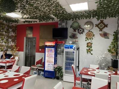 محل تجاري  للبيع في المدينة العالمية، دبي - Hot deal for investment  running restaurant with decent furniture for sale