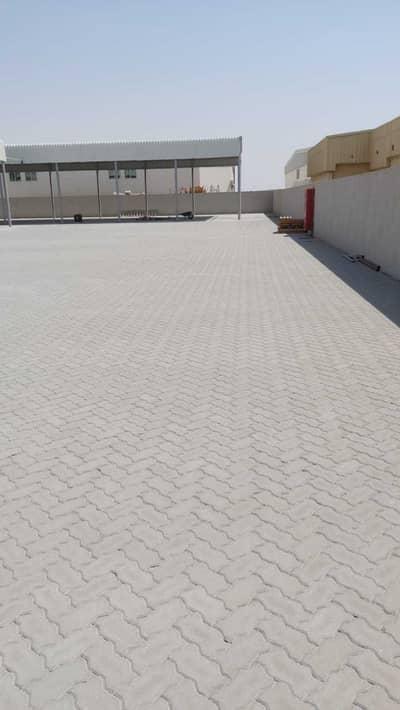 ارض صناعية  للايجار في مدينة الإمارات الصناعية، الشارقة - للايجار حوطة مه مظلة  في الصجة الحنو بلوك 4 مقابل سكراب