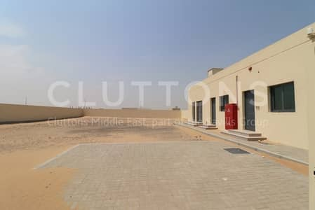 Plot for Rent in Emirates Industrial City, Sharjah - Fenced spacious plot with office and parking